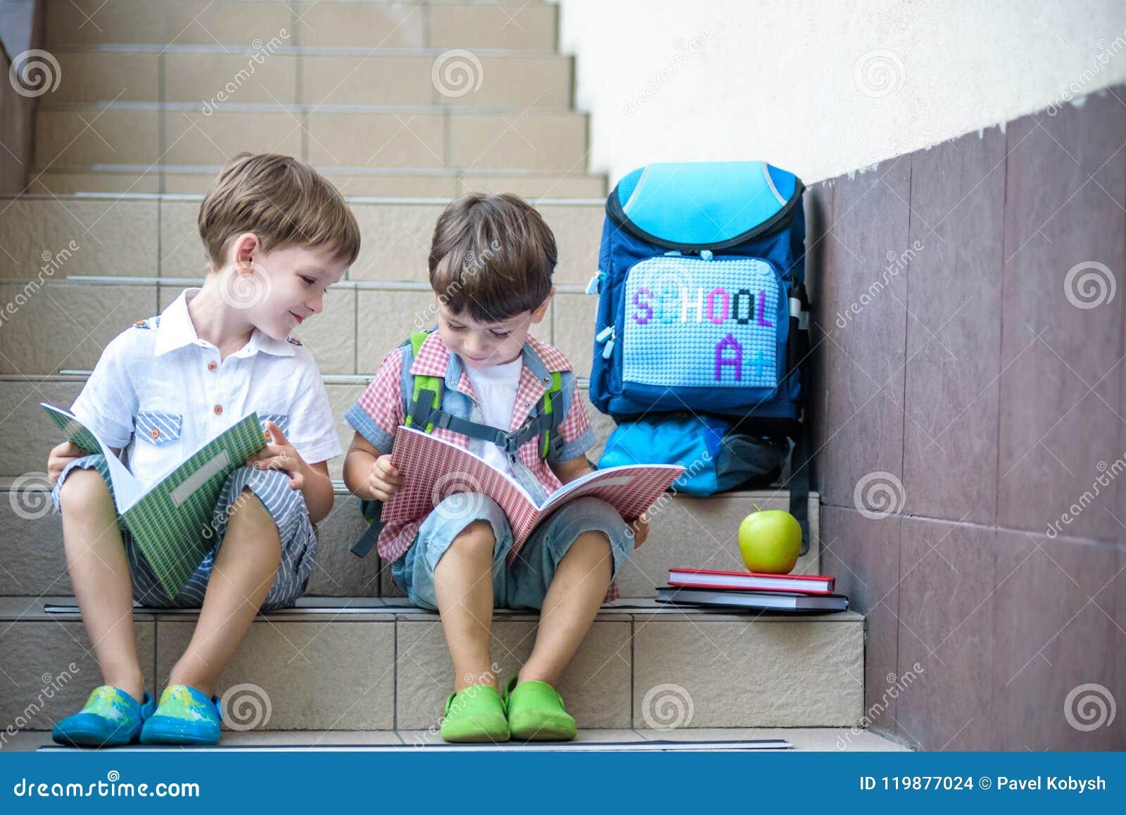 Kinder gehen zurück zur Schule Anfang des neuen Schuljahres nach Sommerferien Zwei Freunde mit Rucksack und Büchern auf erstem sc