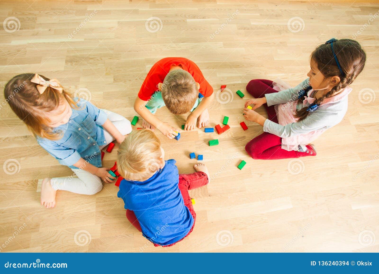 Kinder im Kindergartengebäude von den hölzernen Ziegelsteinen