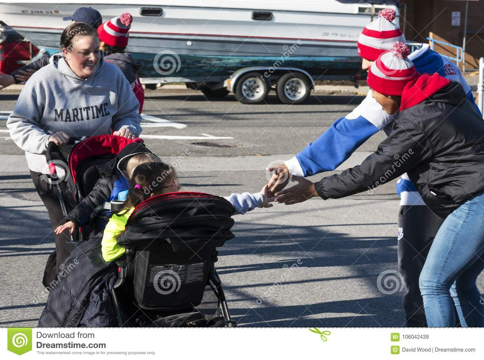 Kinder im Spaziergänger erhalten hohe fives am Ende einer lokalen Danksagung r