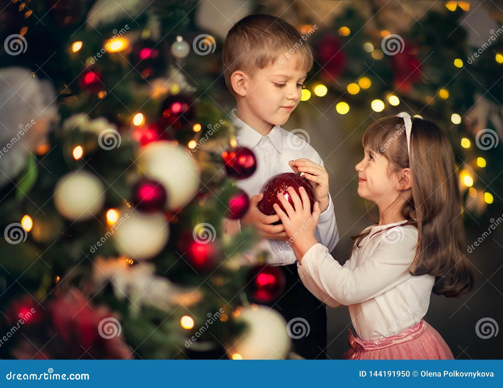 Kinder kleiden oben einen Weihnachtsbaum