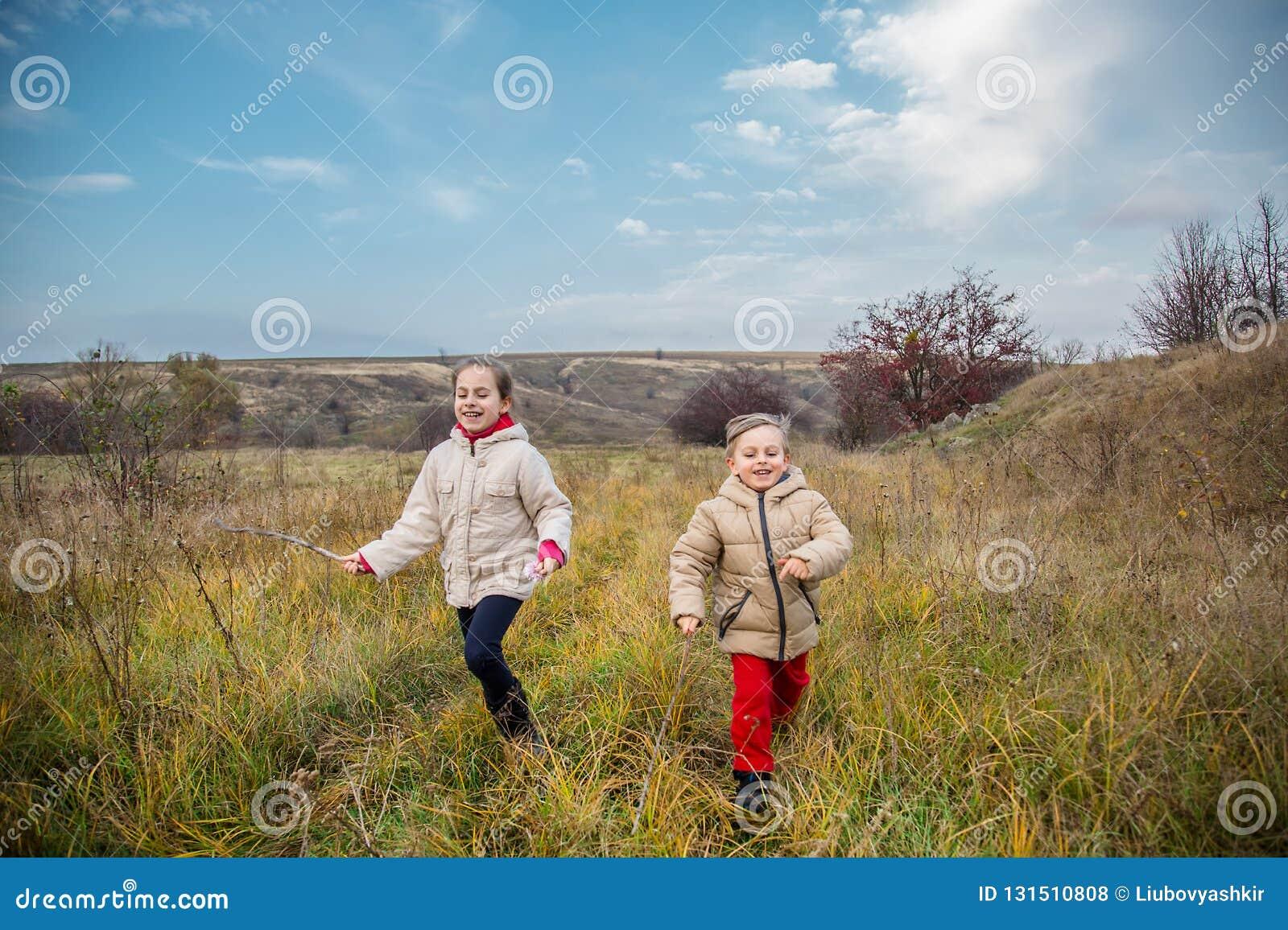 Kinder laufen gelassen in das Feld Kinderspiel auf dem Gebiet an der goldenen Stunde