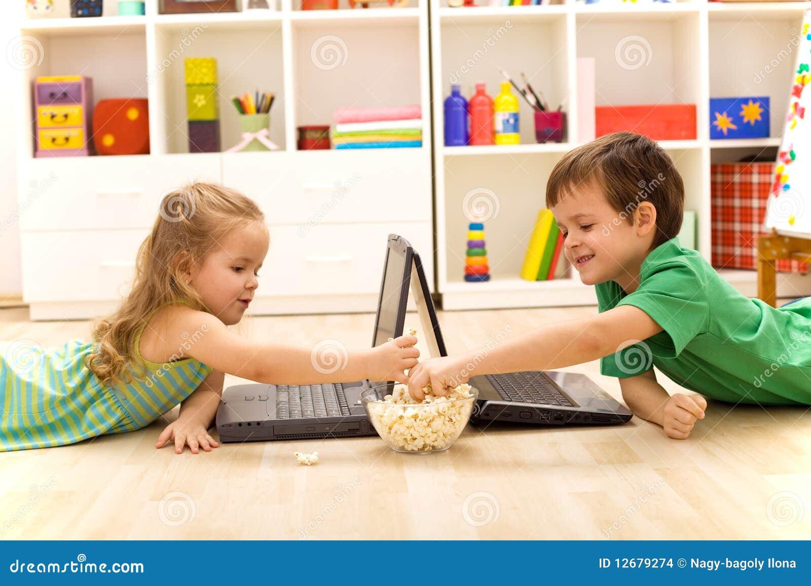Kinder mit Laptopen Popcorn essend