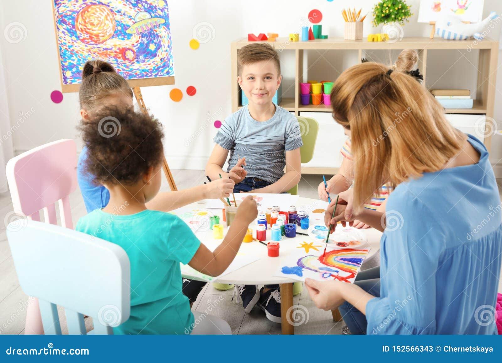 Kinder mit weiblichem Lehrer an malender Lektion