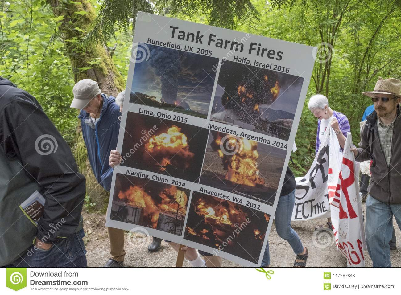 At the Kinder Morgan protest, protesters hold up a poster showing previous tank farm fires