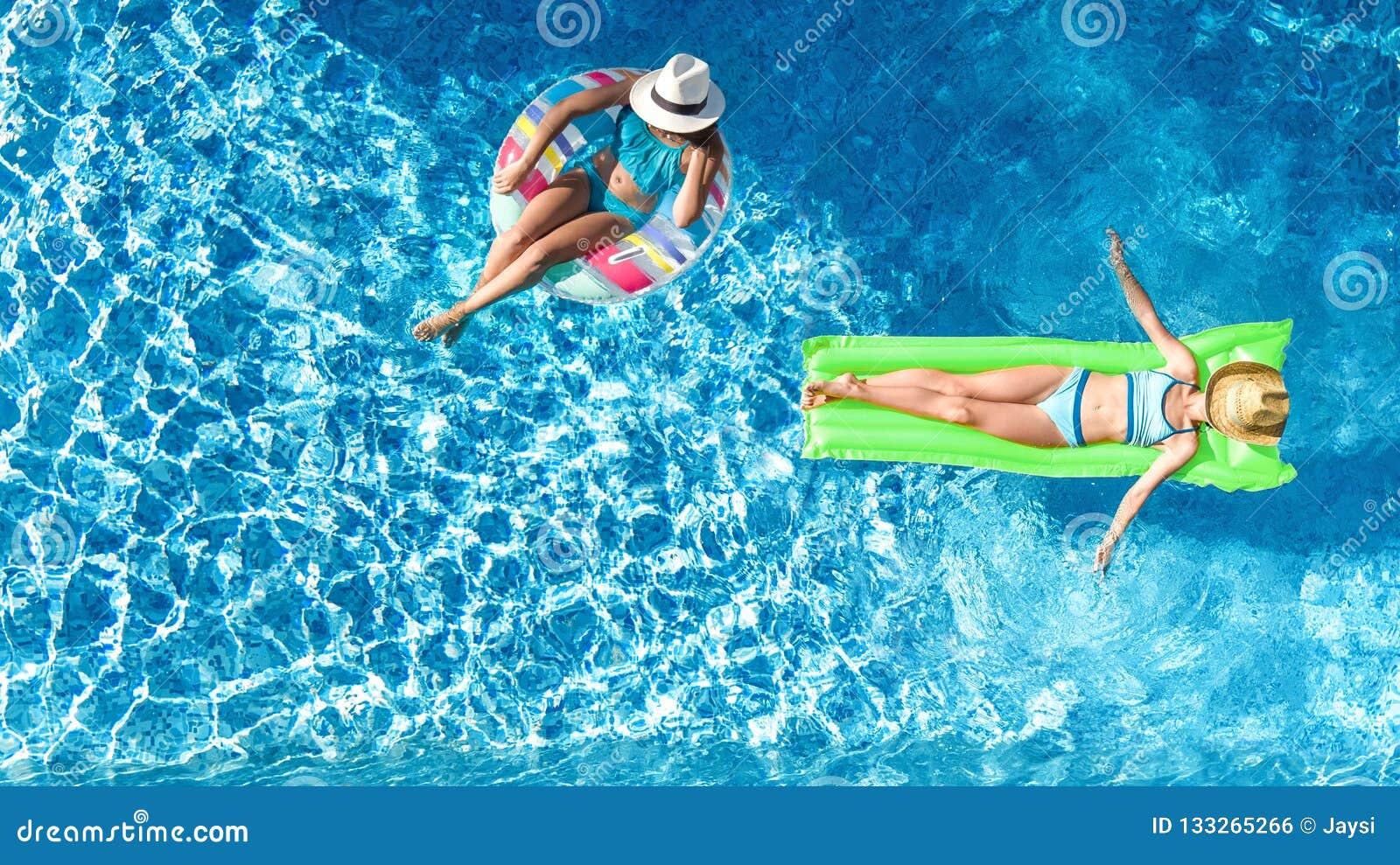 Kinder in Swimmingpoolluftbrummenansicht fom oben, glückliche Kinder schwimmen auf aufblasbarem Ringdonut und Matratze, Mädchen h