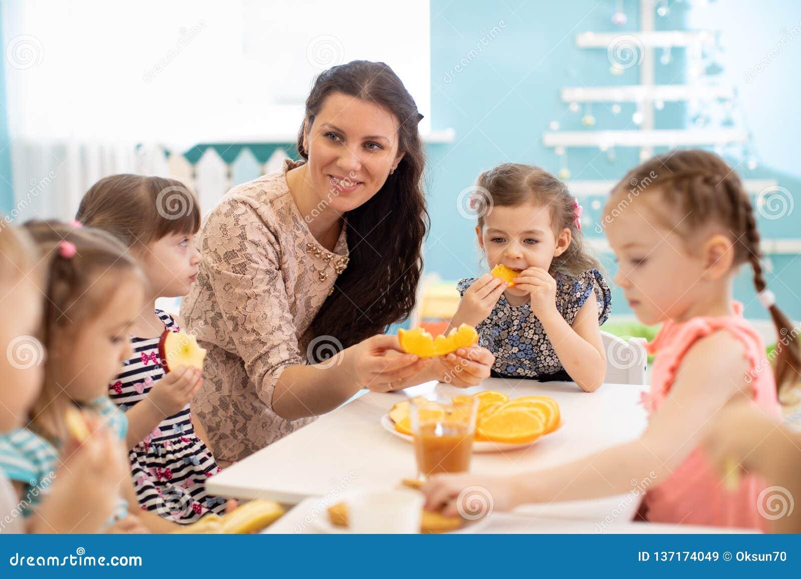 Kinder und Betreuer essen zusammen Frucht als Imbiss im Kindergarten, in der Kindertagesstätte oder im Kindertagesstätte