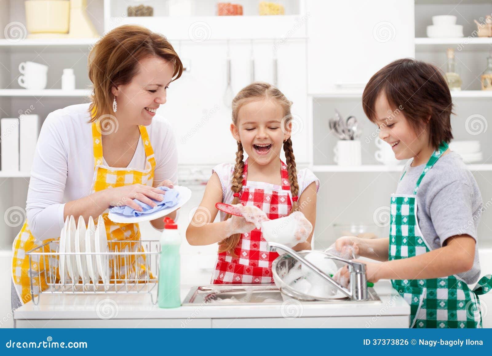Kinder und Mutter, welche die Teller waschen