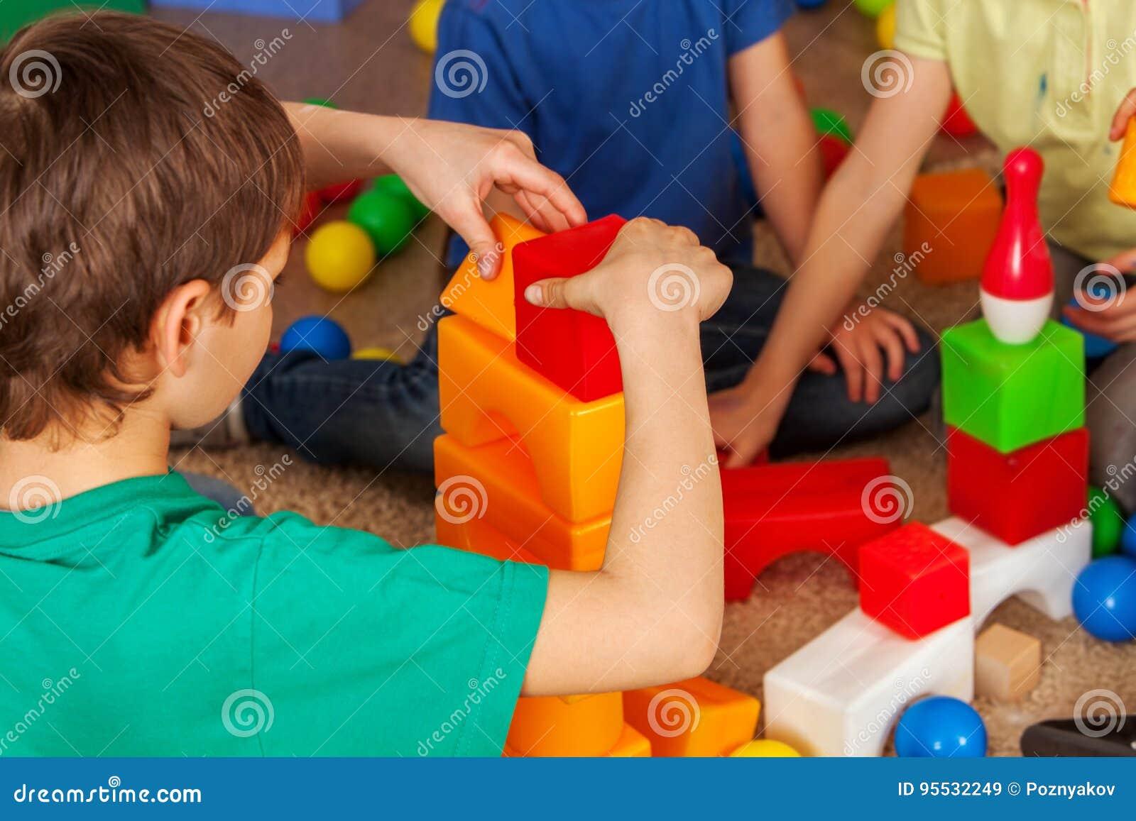 Kinderbausteine im Kindergarten Gruppenkinder, die Spielzeugboden spielen