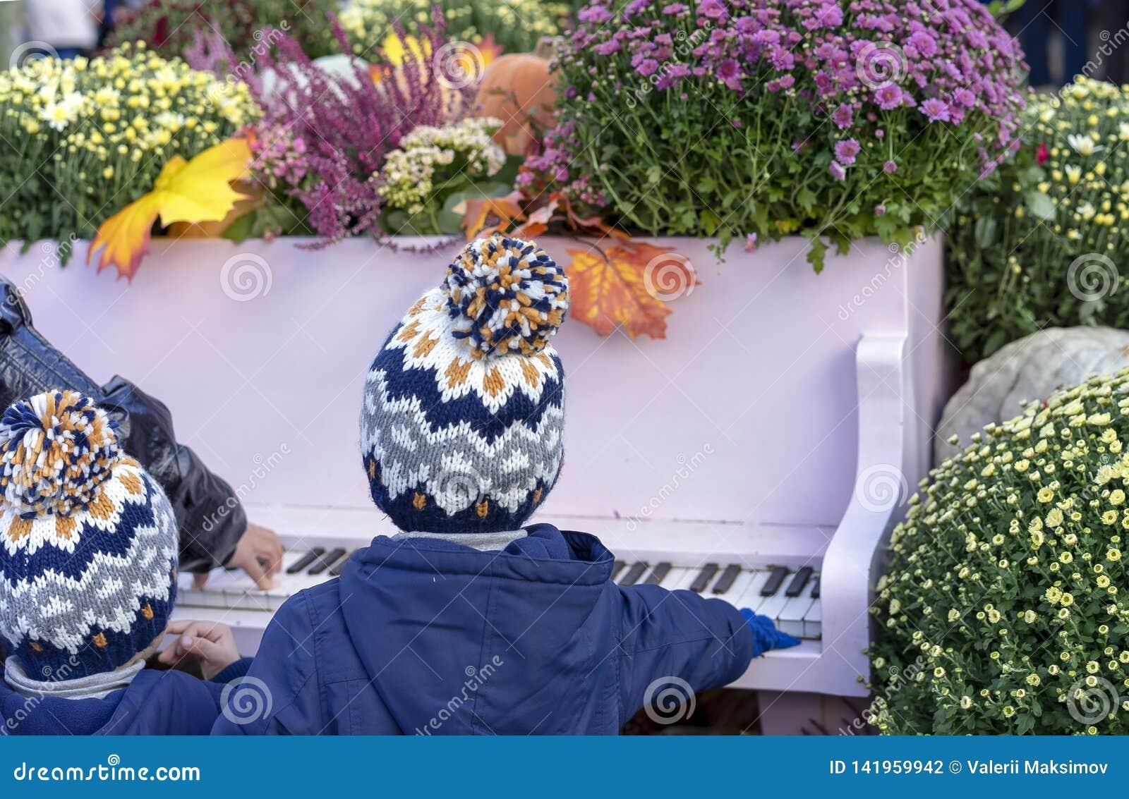 Kinderen in dezelfde hoeden die de piano in de de herfsttuin spelen
