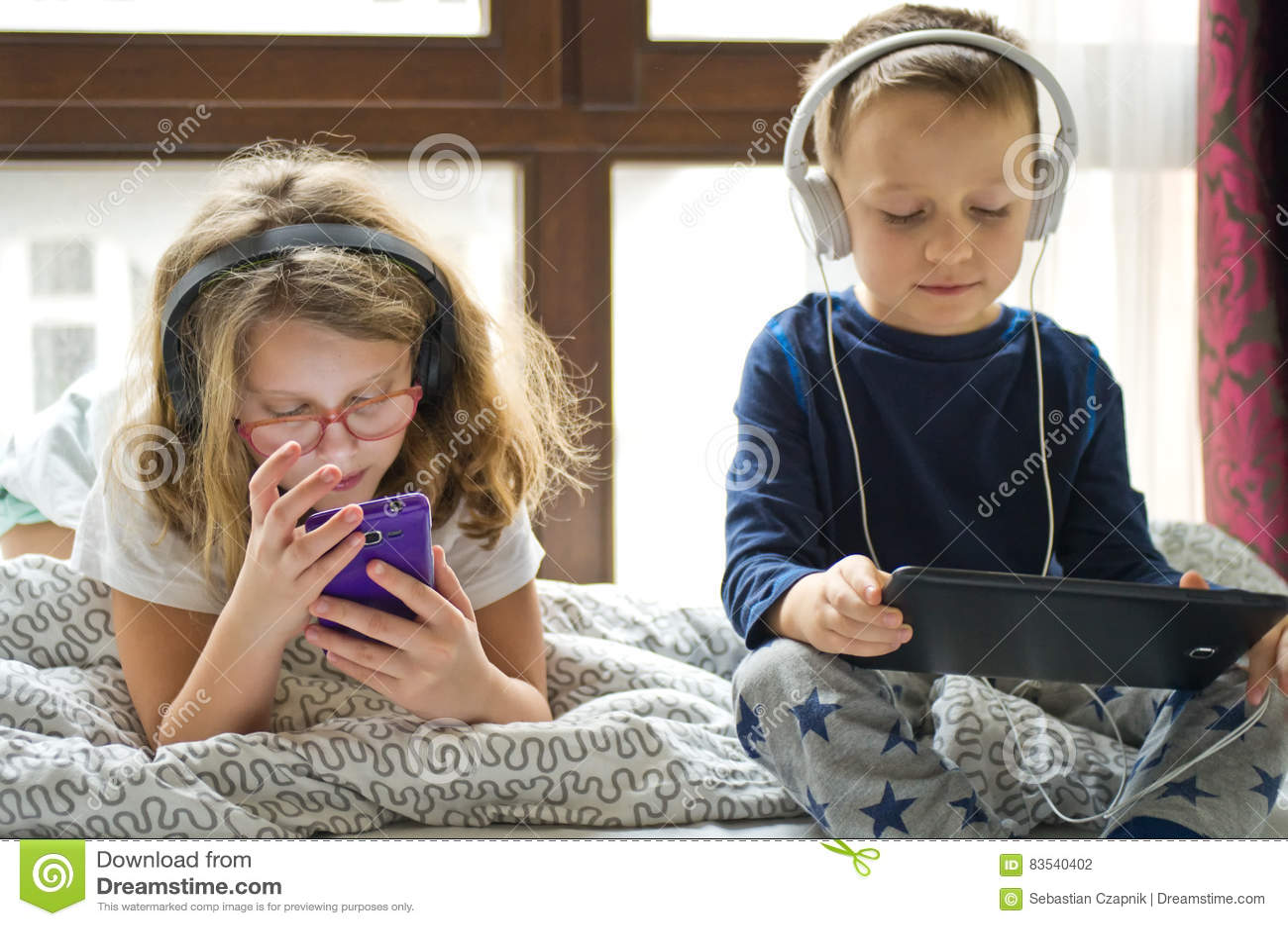 Kinderen die in bed met hun tabletten en telefoons spelen