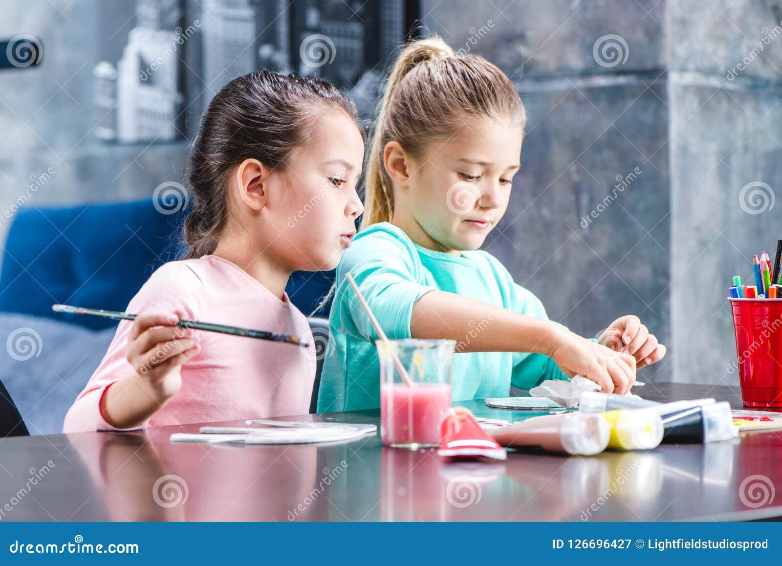 Kinderen die bij lijst en het schilderen dieren zitten