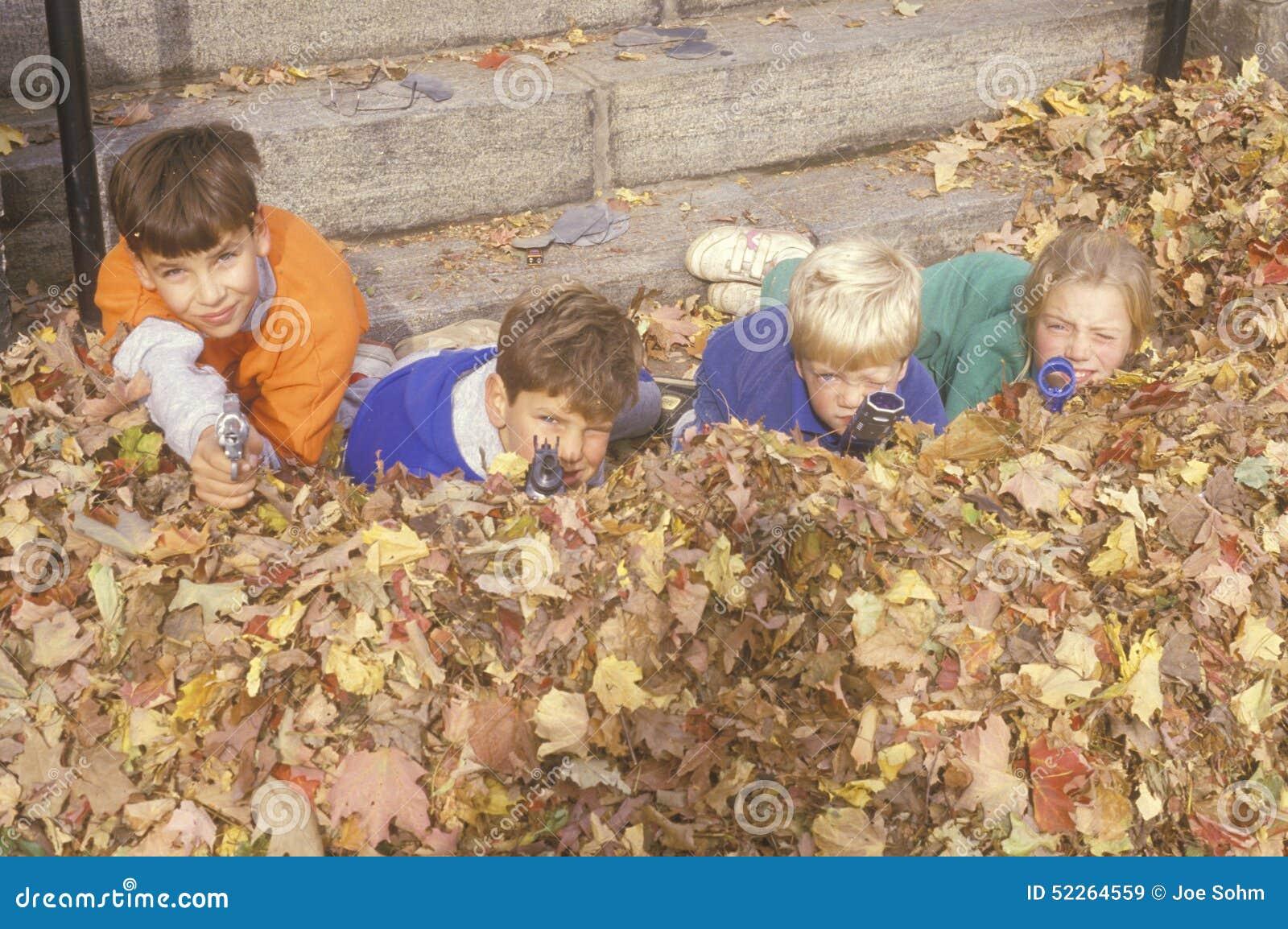 Kinderen die in de herfstbladeren stuk speelgoed kanonnen, Westpoint, NY streven