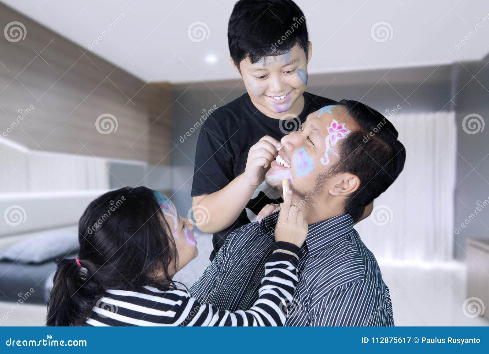Kinderen die gezicht het schilderen doen aan hun vader stock