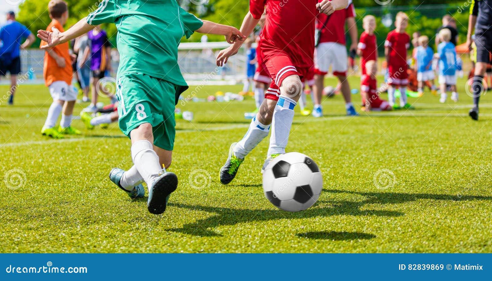 Kinderen die het Spel van het Voetbalvoetbal op Sportterrein spelen De jongens spelen Voetbalgelijke op Groen Gras De Toernooient