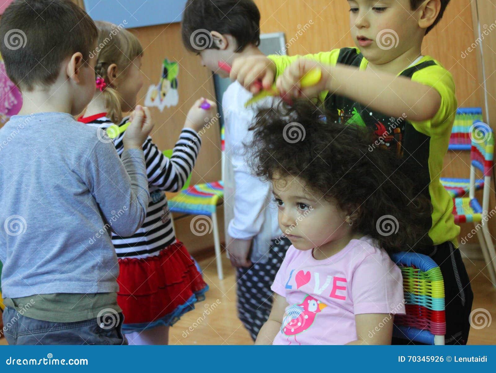Kinderen die in kleuterschool de kapper spelen