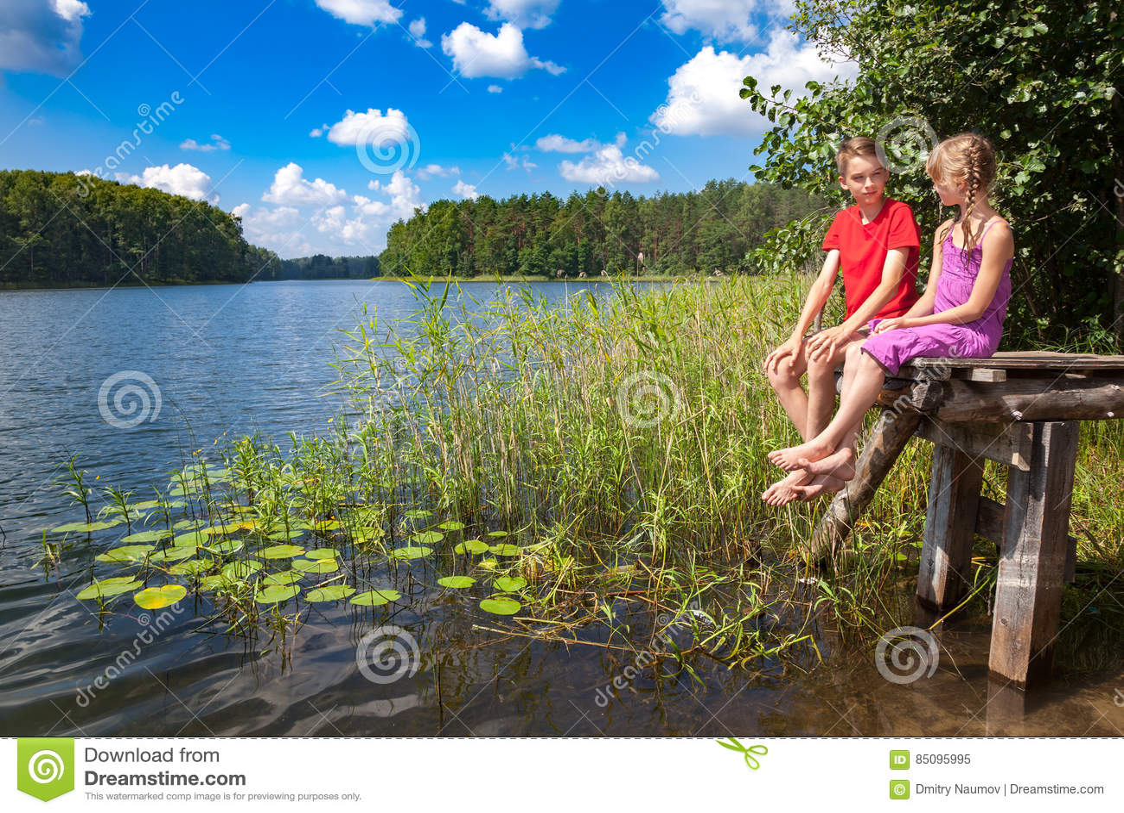 Kinderen die op een pijler door een de zomermeer zitten