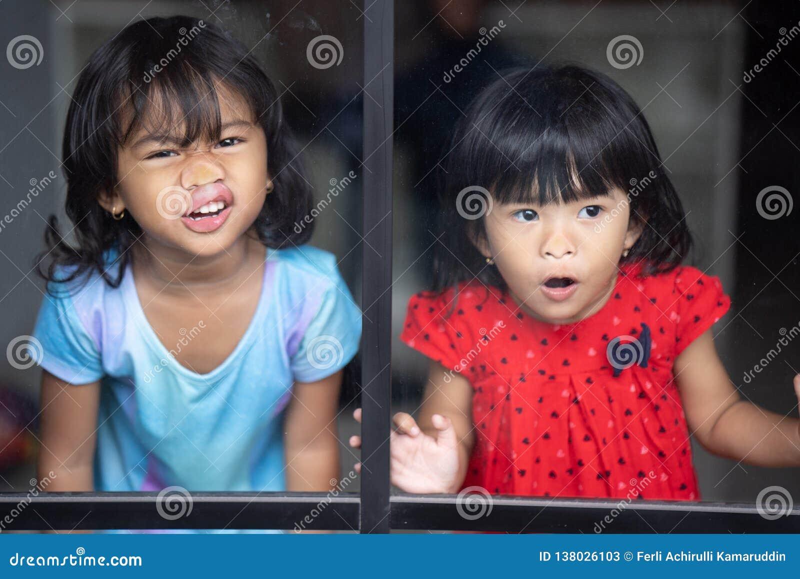 Kinderen die piggy gezicht maken tegen venster