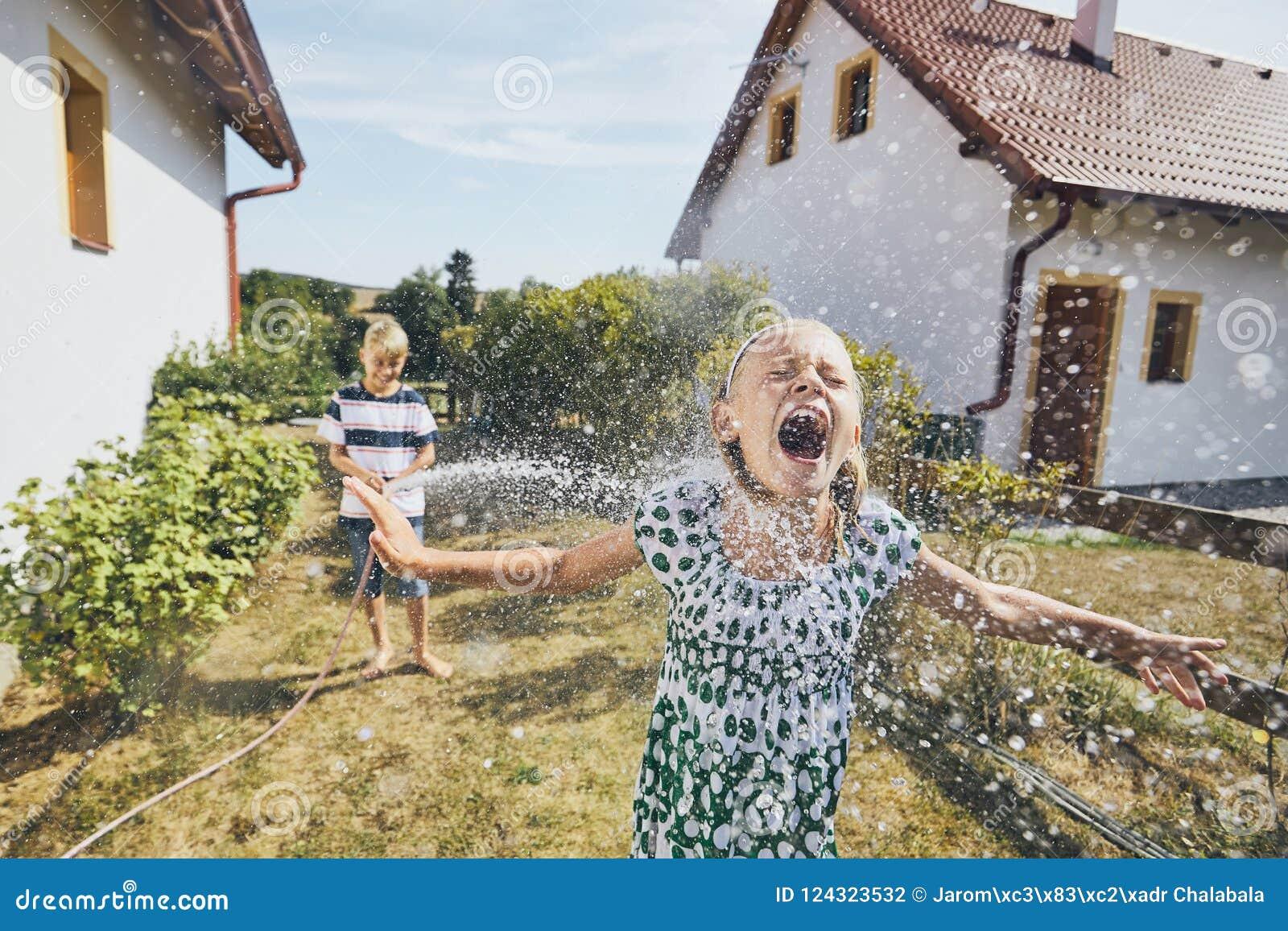 Kinderen die pret met het bespatten van water hebben