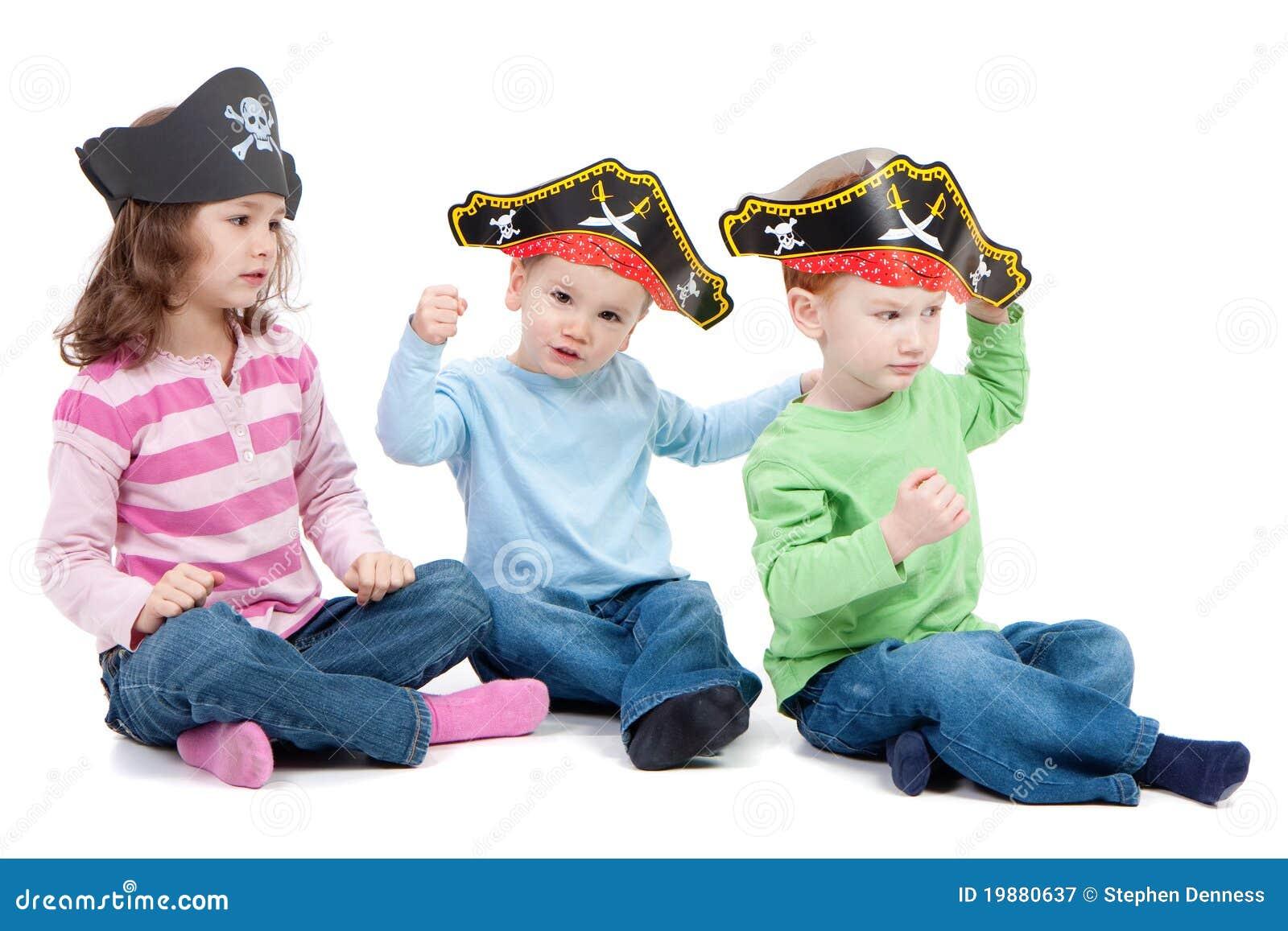 Kinderen die spel in de piraathoeden van de jonge geitjespartij spelen