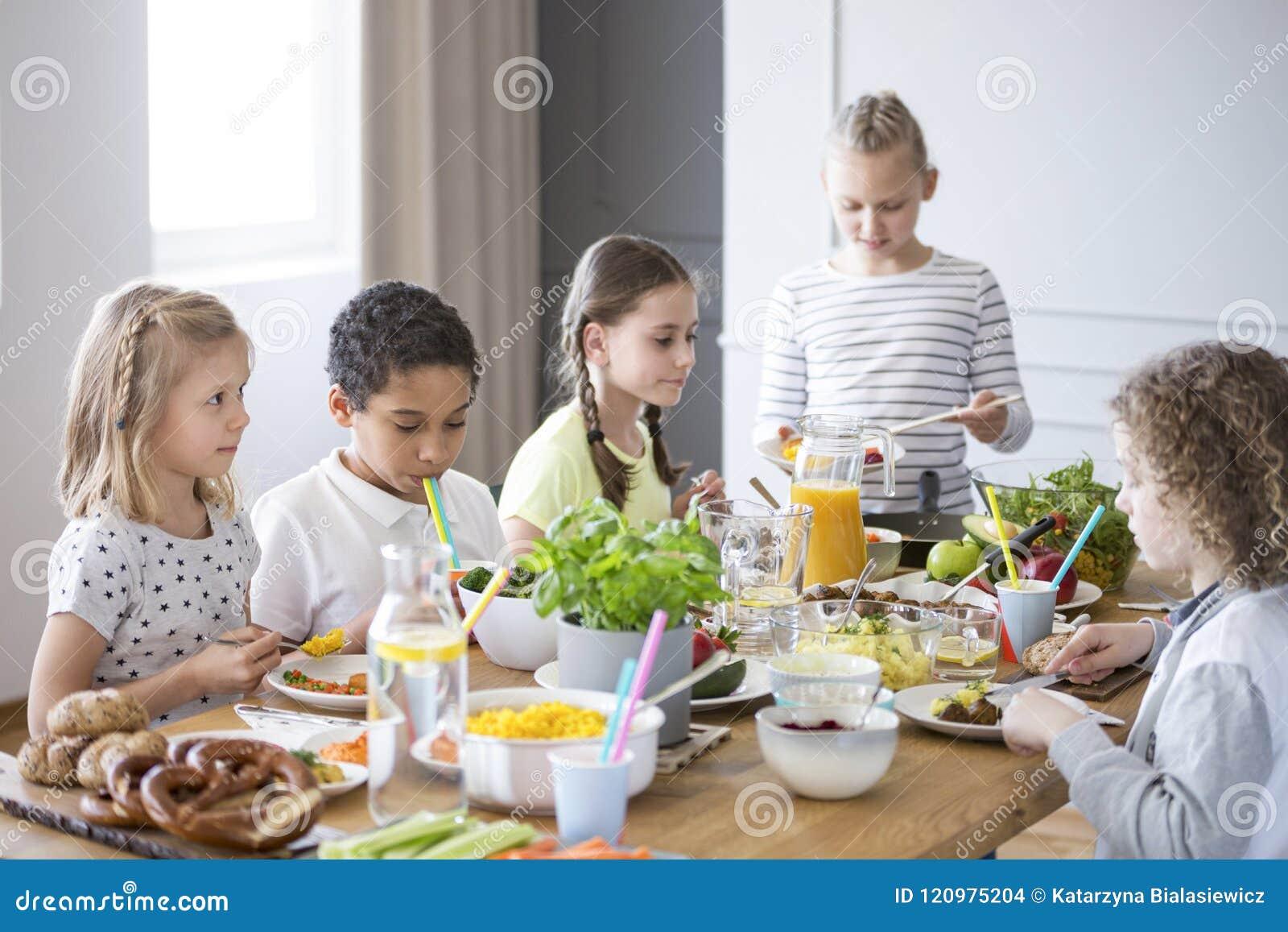 Kinderen die van een gezonde maaltijd genieten door een lijst in een eetkamer dur