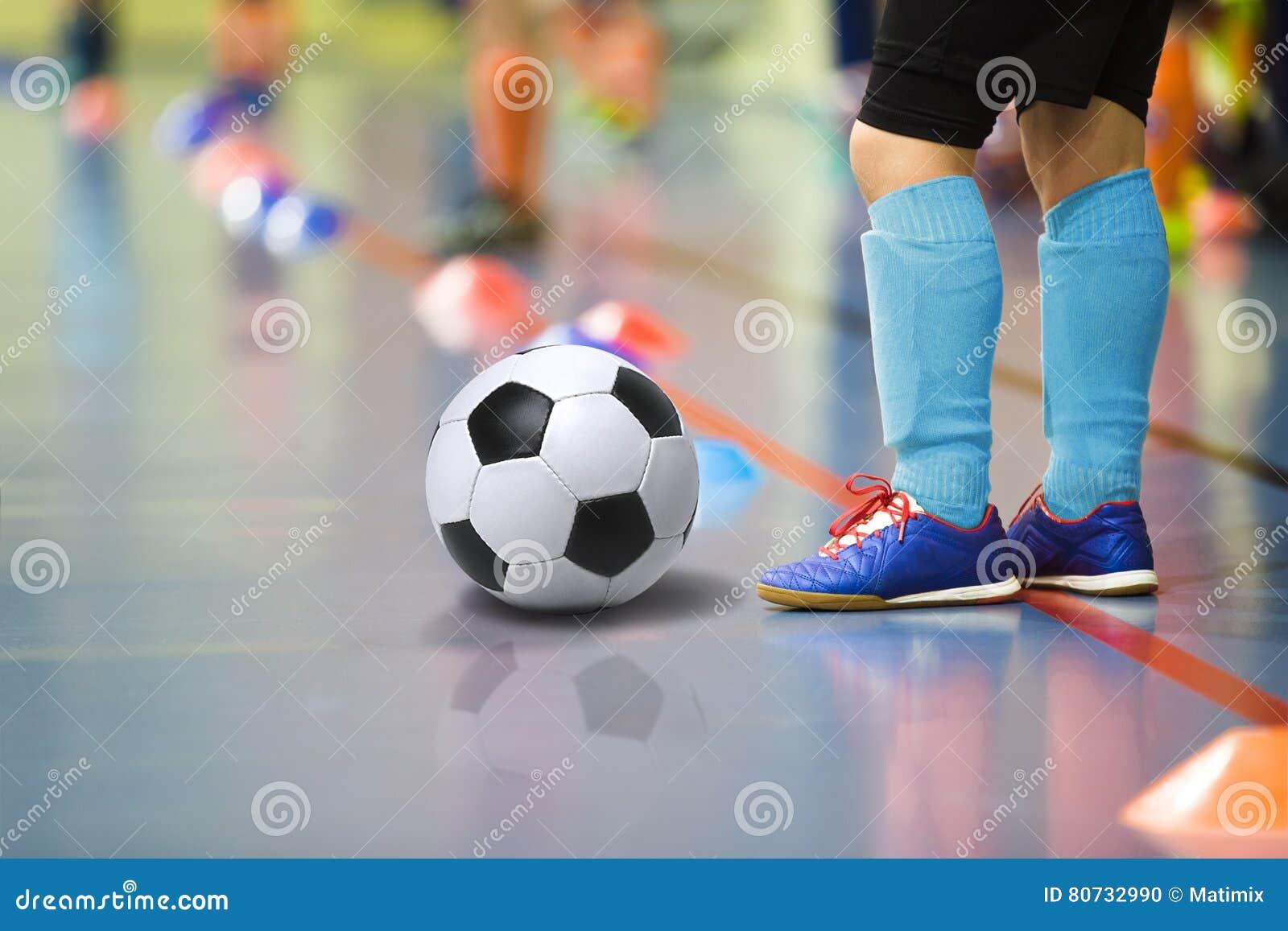 Kinderen die voetbal futsal binnengymnastiek opleiden Jonge jongen die met voetbalbal binnenvoetbal opleiden Weinig speler in lic