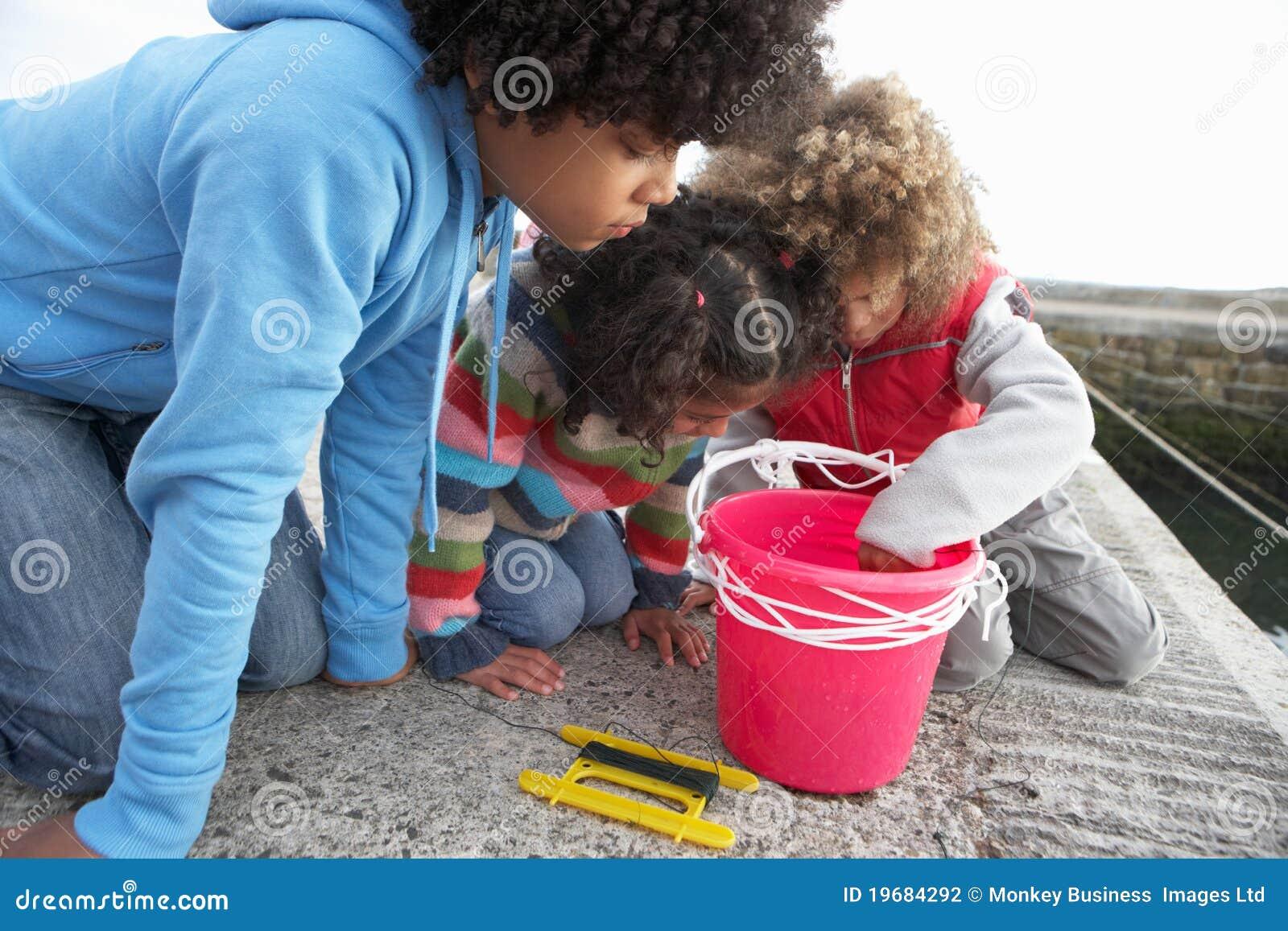 Kinderen die voor krabben vissen