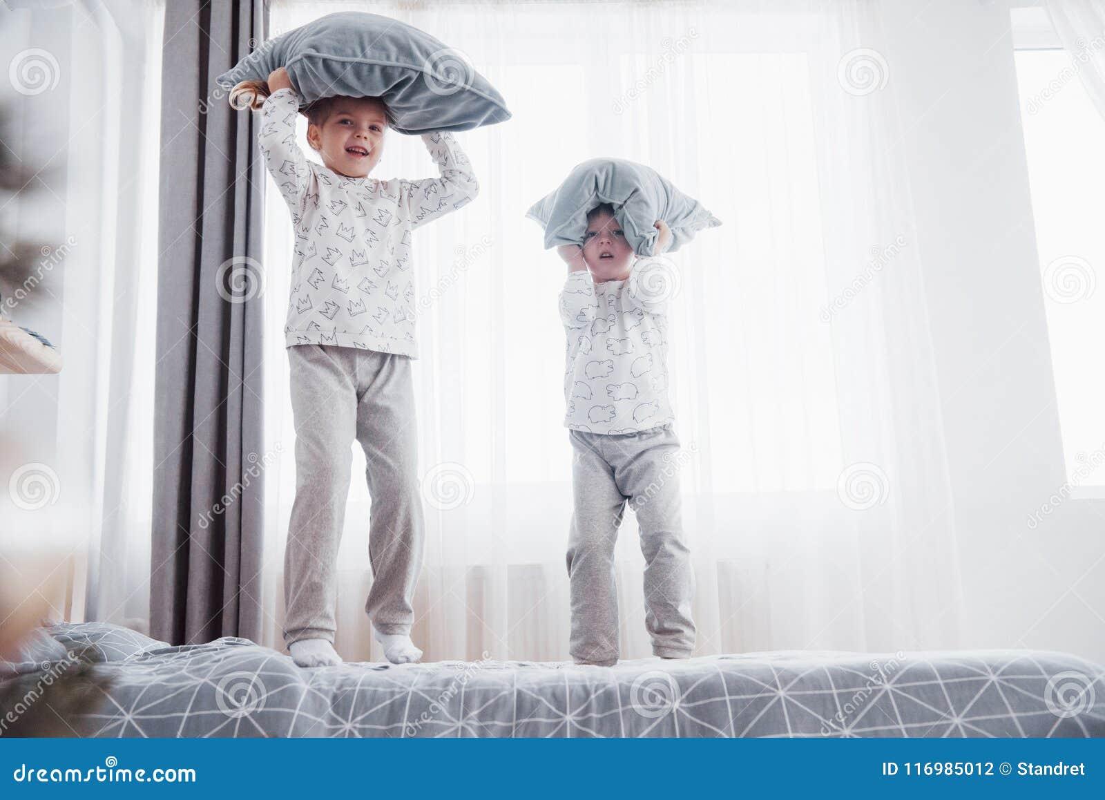 Kinderen die in zachte warme pyjama s in bed spelen