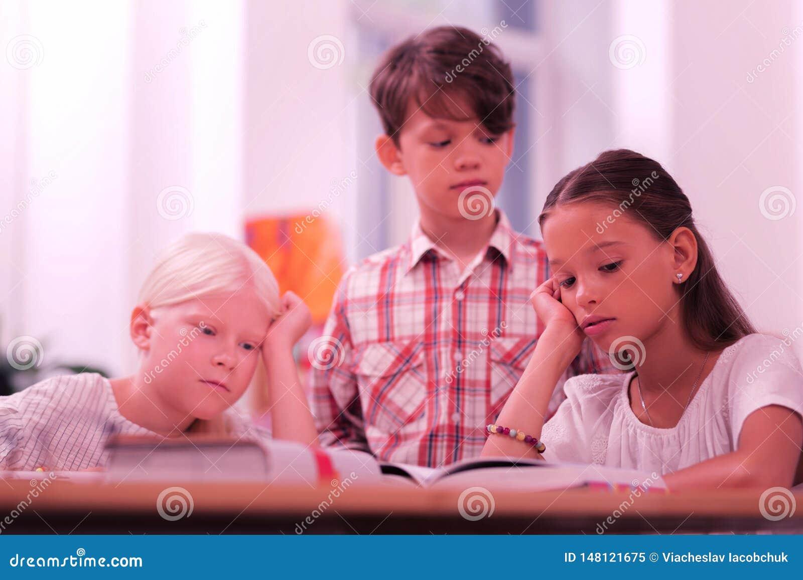 Kinderen in een klaslokaal die het boek proberen te lezen