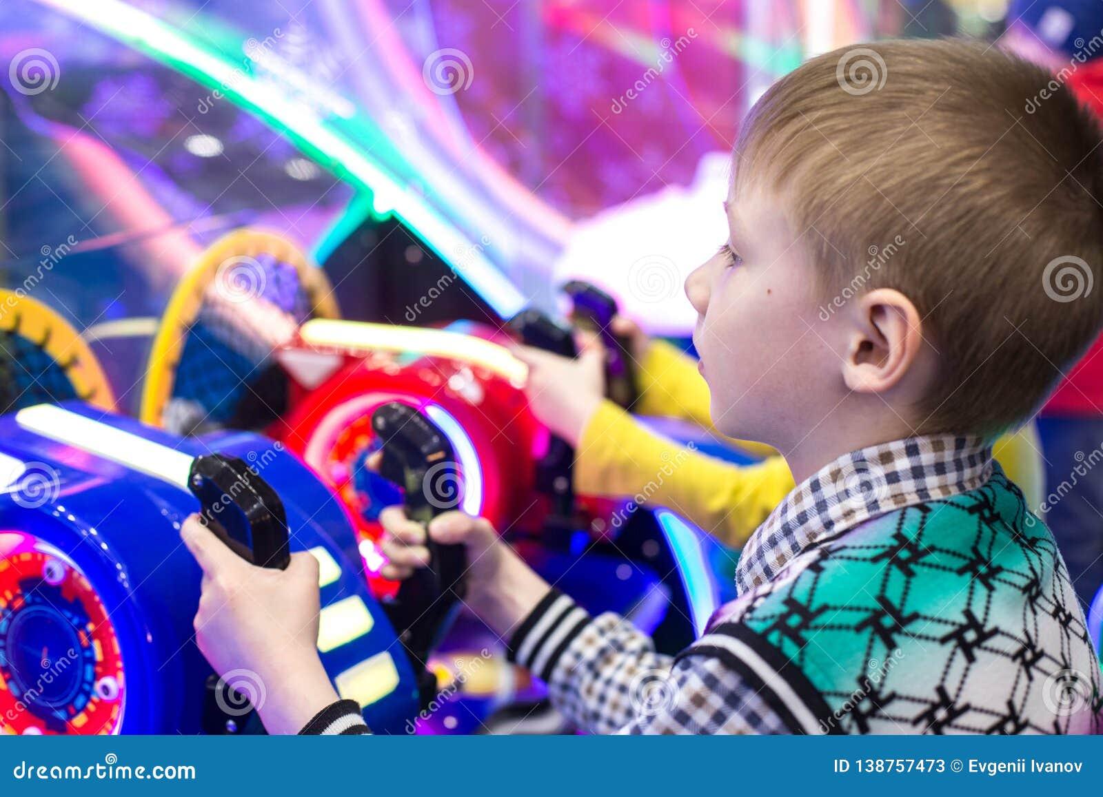 Kinderen en volwassenenspel op de gokautomaten, aantrekkelijkheden in het winkelcentrum De families met kinderen hebben pret en s