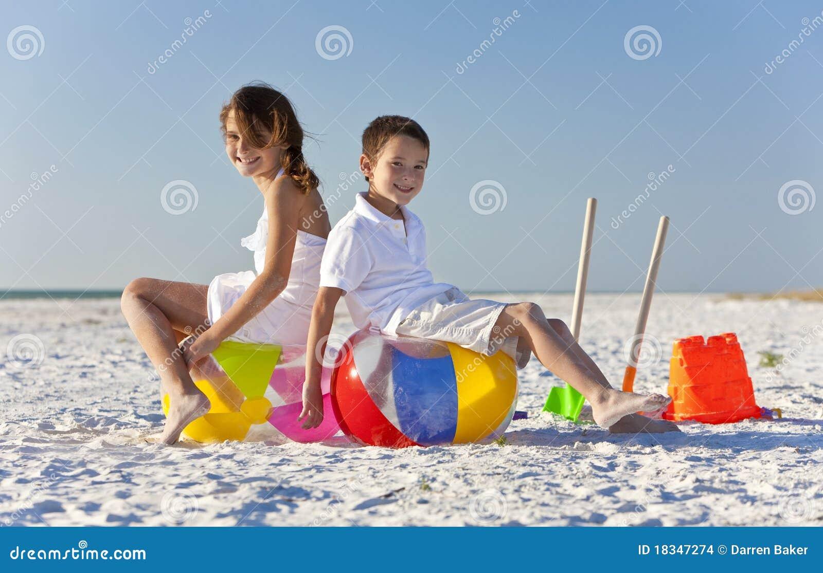 Kinderen jongen en meisje dat op een strand spelen stock afbeeldingen afbeelding 18347274 - Twee meisjes en een jongen ...