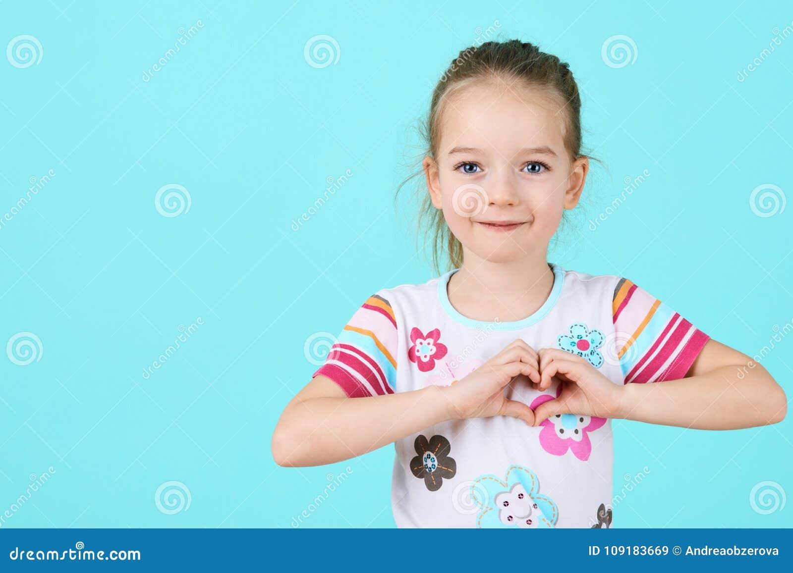 Kinderen, Liefdadigheid, Gezondheidszorg, Goedkeuringsconcept Glimlachend meisje die hart-vorm gebaar maken