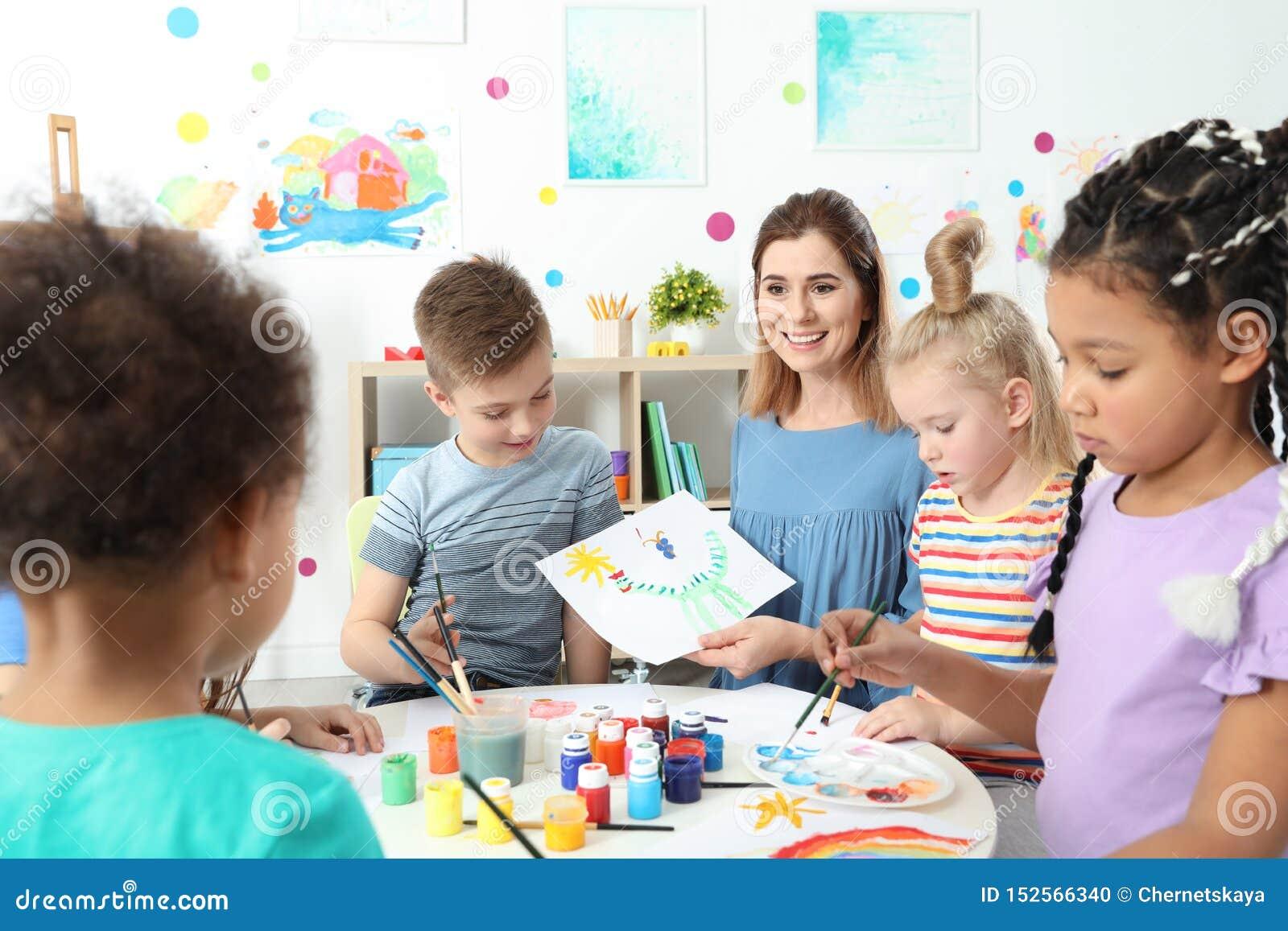 Kinderen met vrouwelijke leraar bij het schilderen les