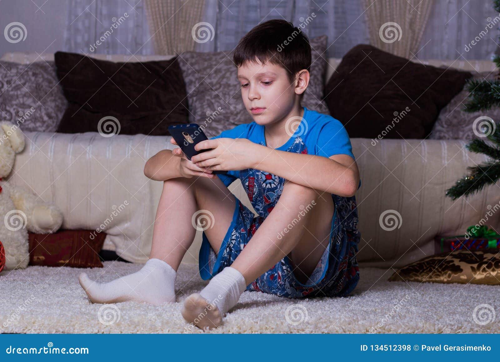 Kinderen, technologie, Internet-mededeling en mensenconcept - jongen met smartphone texting bericht of speelspel thuis