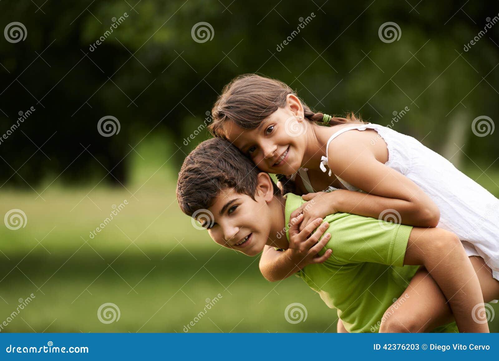 Kinderenjongen en meisje in liefde die op de rug park in werking stellen