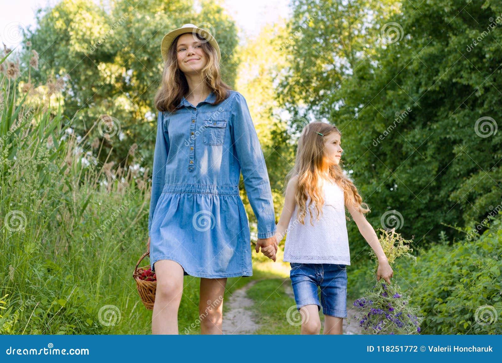 Kinderenmeisjes op de handen van de boswegholding Zonnige de zomerdag, de mand van de meisjesholding met bessen