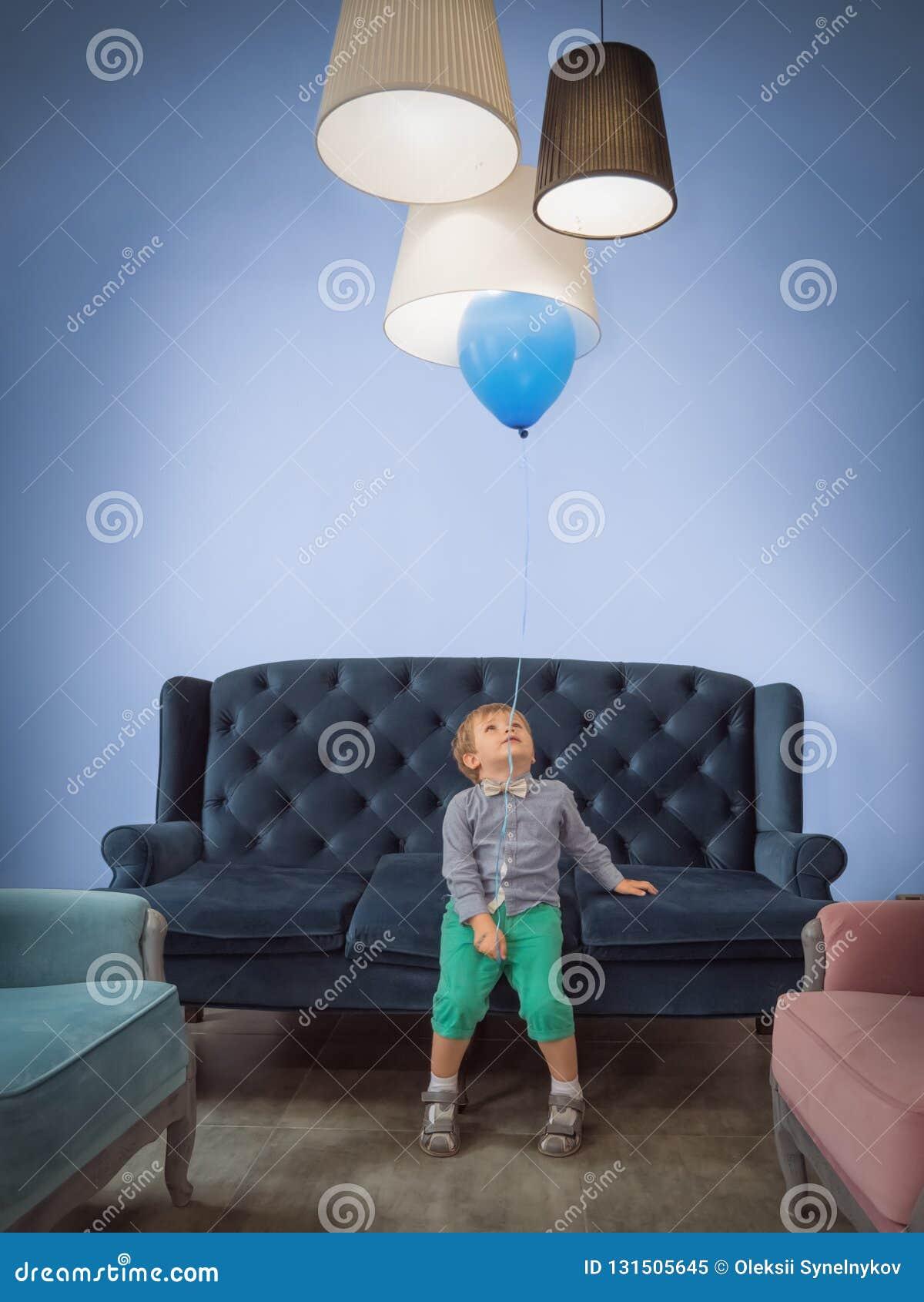 Kinderfeierhintergrund Glückliches Kindheitkonzept Netter Junge mit dem Ballon, der Spaß zu Hause hat