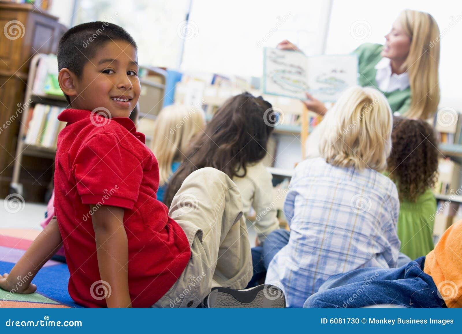Kindergärtnerin, die zu den Kindern liest