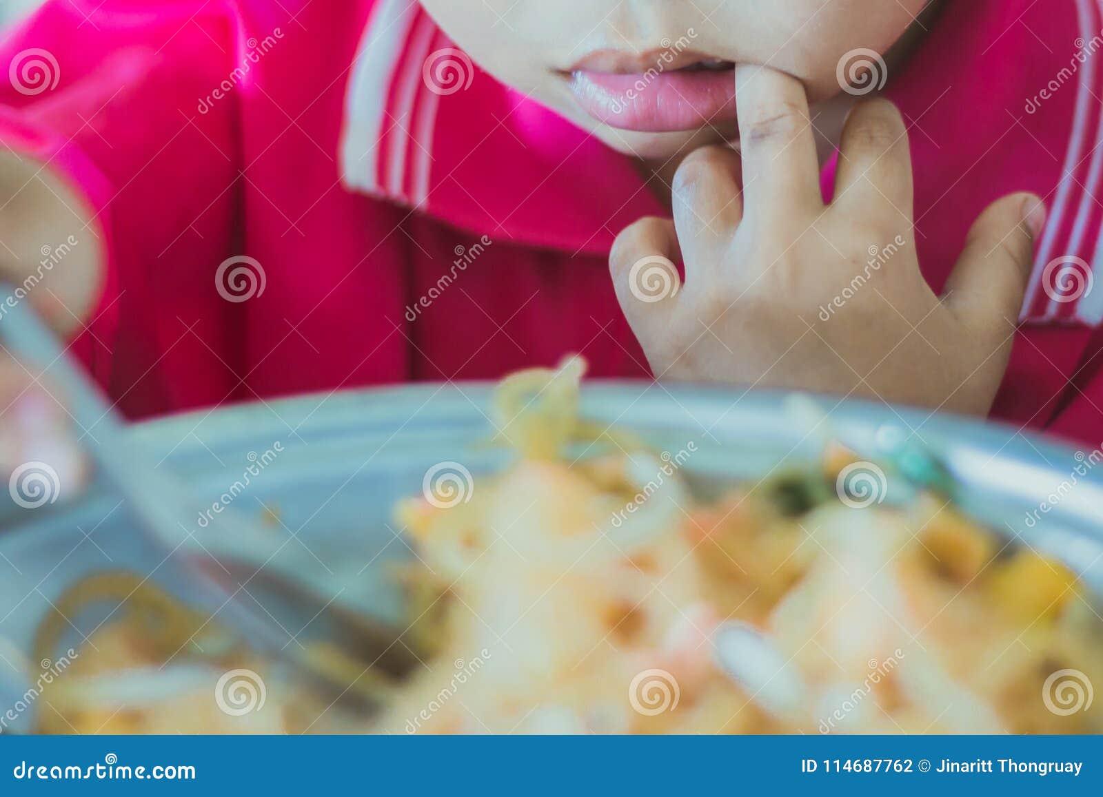 Kindergarten student is eating Pad Thai
