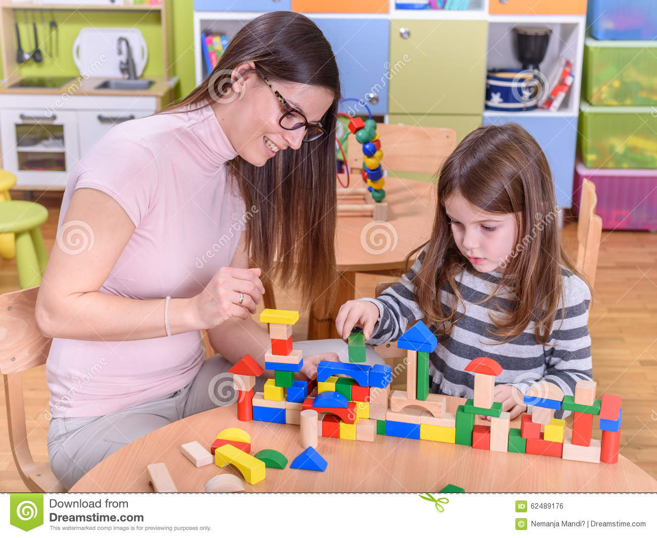 Toys For Teachers : Kindergarten teacher playing with child toy blocks