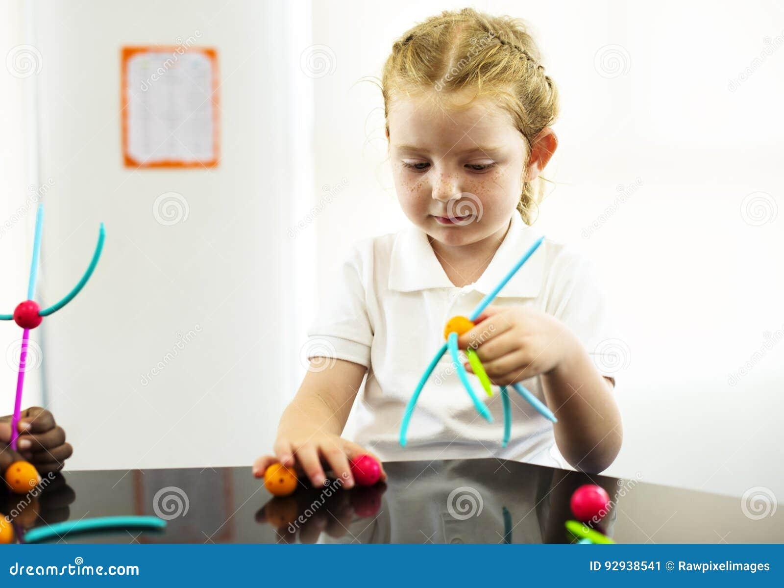 Kindergartenstudent, der das Lernen von Strukturen von den Spielwaren hält