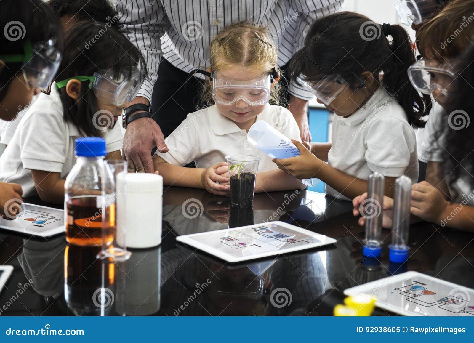 Kindergartenstudenten, die Experiment pflanzend lernen
