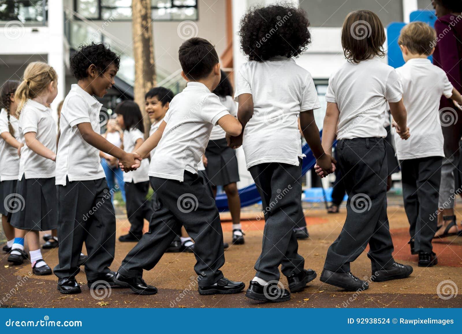 Kindergartenstudenten, die Händchenhalten stehen