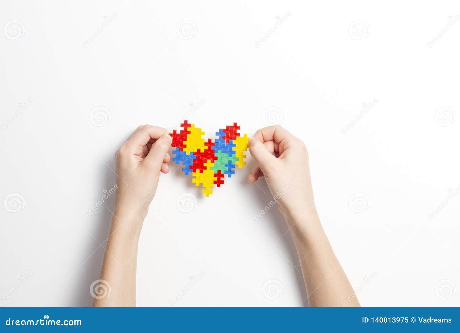 Kinderhände, die buntes Herz auf weißem Hintergrund halten Weltautismusbewusstseins-Tageskonzept