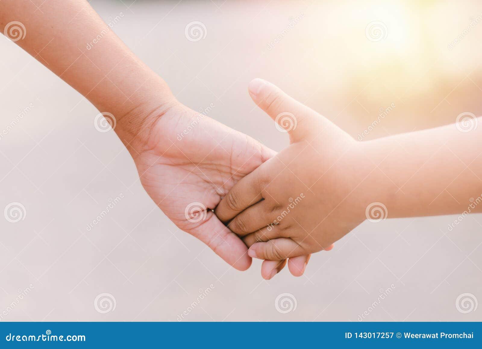 Kinderhändchenhalten beim Gehen bei Sonnenuntergang