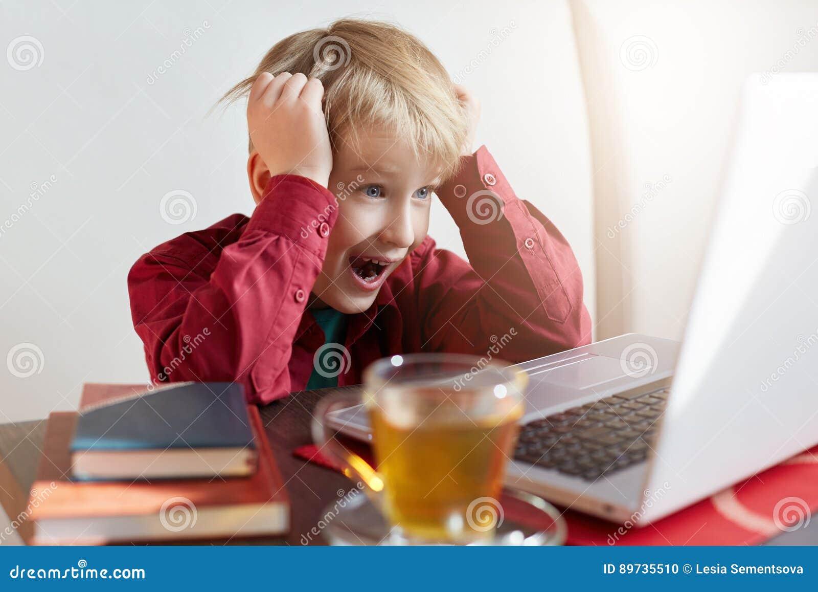 Kinderjaren, moderne technologie, Internet en onderwijsconcept Het emotionele aanbiddelijke blonde mannetje die kijkt, bestuderen