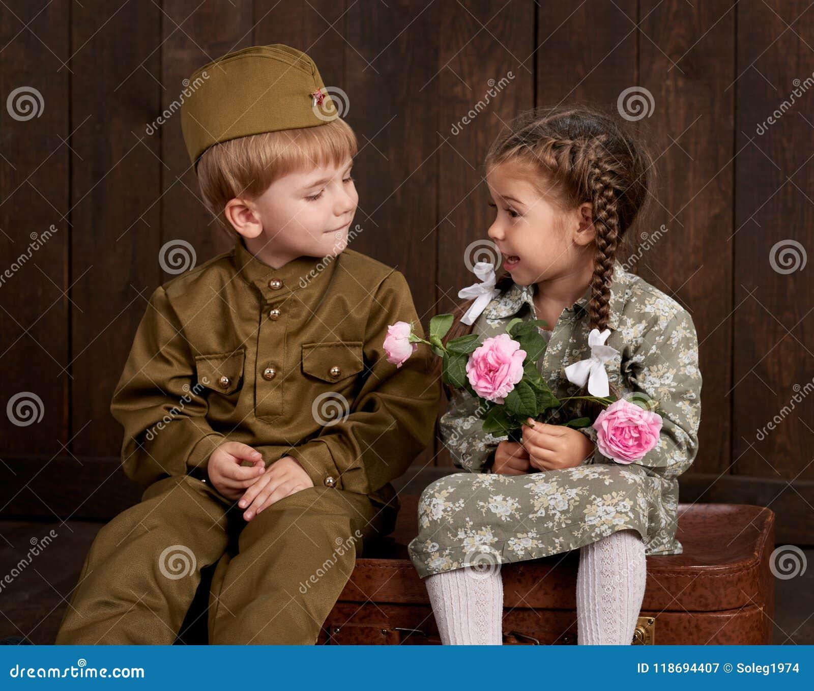 Kinderjunge werden wie Soldat in den Retro- Militäruniformen und im Mädchen im rosa Kleid gekleidet, das auf altem Koffer, dunkle