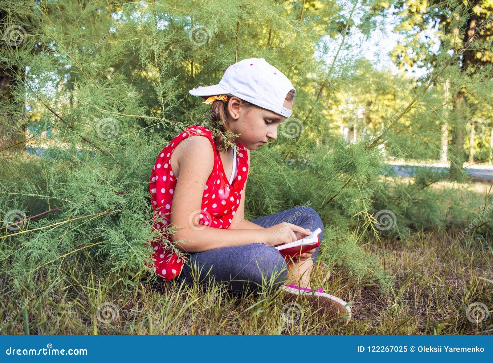 Kinderlesebuch oder -bibel draußen Nettes kleines Mädchen, welches die Bibel liest