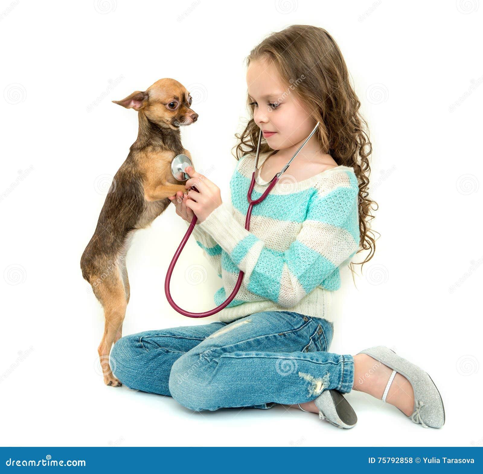Kindermädchen, das Tierarzt mit ihrem kleinen Hund spielt