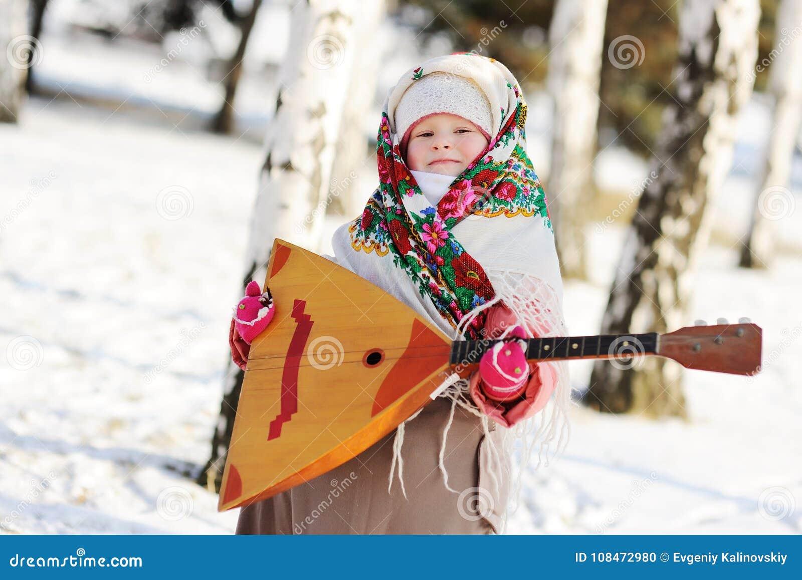 Kindermädchen in einem Pelzmantel und in einem Schal auf russisch mit einer Balalaika
