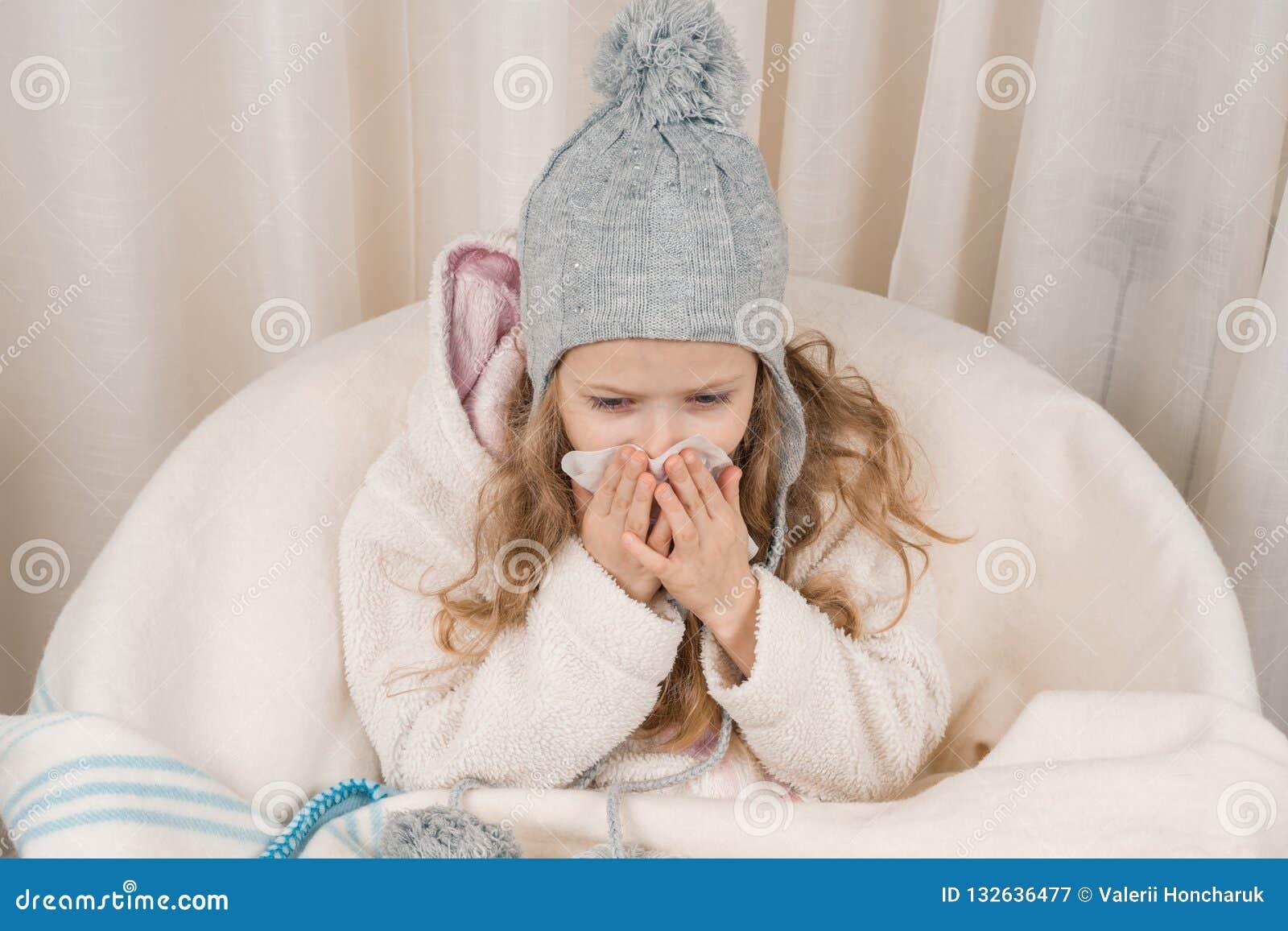Kindermädchen zu Hause im Stuhl mit woolen umfassendem Niesen der warmen Strickmütze im Taschentuch Jahreszeitherbst-Winterkälten